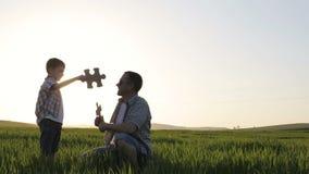 Vader en zoon die op het gebied in de zonsondergangtijd lopen stock videobeelden