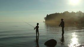 Vader en zoon die op het meer vissen stock videobeelden