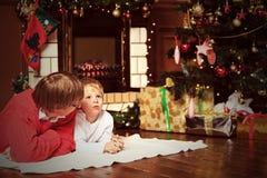 Vader en zoon die op Kerstmis spreken Stock Foto