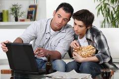 Vader en zoon die op TV letten royalty-vrije stock afbeeldingen