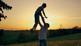 Vader en zoon die pret hebben bij zonsondergang op het gebied stock video