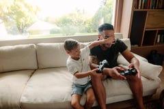 Vader en zoon die pret het spelen videospelletjes hebben thuis royalty-vrije stock afbeelding