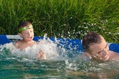 Vader en zoon die pret in het zwembad hebben Royalty-vrije Stock Foto