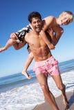 Vader en Zoon die Pret op Strand hebben stock foto