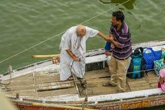 Vader en zoon die rit in heilige rivier Ganga nemen stock afbeelding
