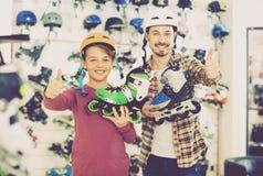 Vader en zoon die rolschaatsen tonen kochten zij sportenopslag in royalty-vrije stock foto