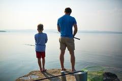 Vader en zoon die samen op meer vissen stock afbeelding