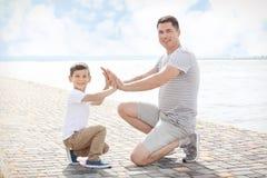Vader en zoon die slaand handenspel spelen Stock Afbeelding