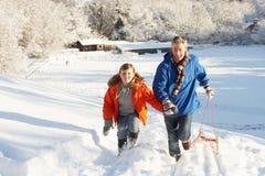 Vader en Zoon die SneeuwHeuvel van de Slee trekken de omhoog Stock Foto's