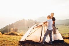 Vader en zoon die tent installeren op bosopen plek Trekking met het beeld van het jonge geitjesconcept royalty-vrije stock fotografie