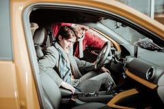 Vader en zoon die verantwoordelijk terwijl het kiezen van nieuwe auto voelen royalty-vrije stock foto