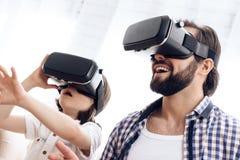 Vader en zoon, die virtuele werkelijkheidsglazen de de gebruiken, spelen een interactief spel stock afbeeldingen
