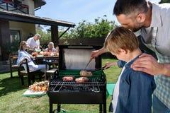 Vader en zoon die vlees in openlucht roosteren terwijl familiezitting bij lijst royalty-vrije stock foto's
