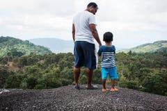 Vader en zoon die zich op berg bevinden royalty-vrije stock foto's