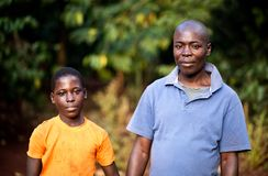Vader en zoon in een dorp in Oeganda stock foto's