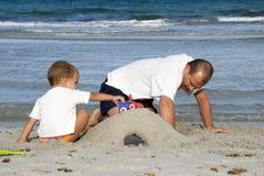 Vader en zoon in het strand Stock Foto's