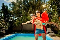 Vader en zoon in kostuums van superheroes in de pool stock foto
