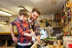 Vader en zoon met beitel die op workshop werken royalty-vrije stock afbeeldingen
