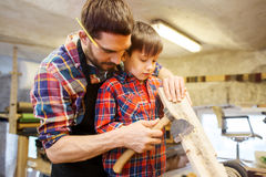 Vader en zoon met bijl en houten plank op workshop stock afbeelding