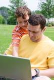 Vader en zoon met computer Stock Foto's