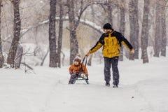 Vader en zoon met een slee openlucht in de sneeuw Stock Fotografie
