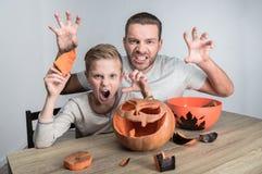 Vader en zoon met Halloween-pompoen stock fotografie