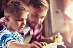 Vader en zoon met het hout van de heersersmaatregel op workshop stock afbeelding