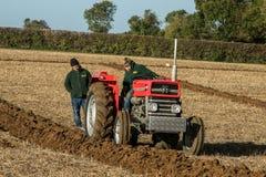 Vader en zoon met het uitstekende rode tractor ploegen Stock Fotografie