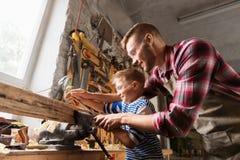 Vader en zoon met rasp die op workshop werken stock afbeelding