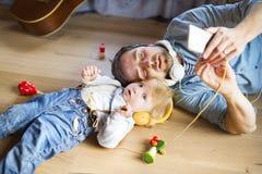Vader en zoon met smartphone en oortelefoons, het luisteren muziek stock fotografie
