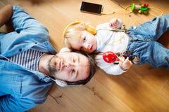 Vader en zoon met smartphone en oortelefoons, het luisteren muziek stock foto