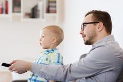 Vader en zoon met verre het letten op TV thuis Royalty-vrije Stock Afbeeldingen