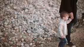 Vader en zoon op de handen van de strandholding en het lopen langs de kust bij zonsondergang Het besteden Tijd samen stock videobeelden