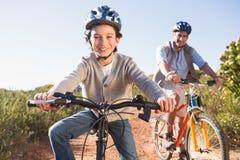 Vader en zoon op een fietsrit stock foto