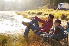 Vader en zoon op een het kamperen reis die door een meer vissen Stock Foto's