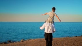 Vader en zoon op het strand bij zonsondergang stock videobeelden