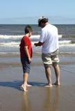 Vader en zoon op strand stock fotografie