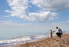 Vader en zoon op strand Royalty-vrije Stock Afbeeldingen