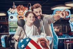 Vader en zoon op stuk speelgoed motorfiets Familierust stock afbeelding