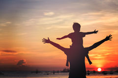 Vader en zoon op zonsondergangstrand Stock Foto's