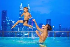 Vader en zoon in openlucht zwembad met stadsmening in blauw s royalty-vrije stock fotografie
