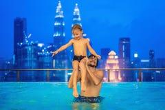 Vader en zoon in openlucht zwembad met stadsmening in blauwe hemel stock foto's