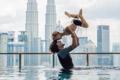 Vader en zoon in openlucht zwembad met stadsmening in blauwe hemel stock foto