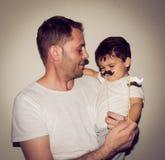 Vader en zoon playng met snor grappige gezichten stock afbeeldingen