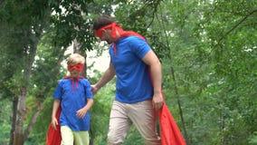 Vader en zoon in superherokostuums hoog-vijf, groepswerkconcept, doel het bereiken stock footage
