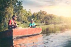 Vader en zoons de holdingshengels en bekijken de oppervlakte van het water van het meer stock afbeelding