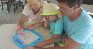 Vader en zoons de horlogemoeder schildert huisdier op magneetraad stock video