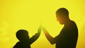 Vader en zoons de schok dient overeenkomst in Gelukkige familie die pret in het avond hebben Mooie aardlandschap stock footage