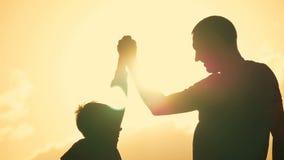Vader en zoons de schok dient overeenkomst in Gelukkige familie die pret in het avond hebben Mooie aardlandschap stock video