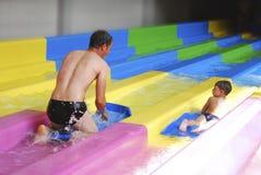 Vader en zoons het berijden in het waterpark met dia's. Stock Foto's
